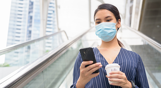 Woman wearing mask looking at smartphone