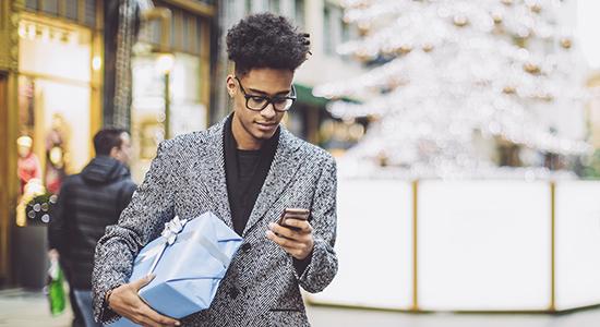 Man looking at smartphone while holiday shopping