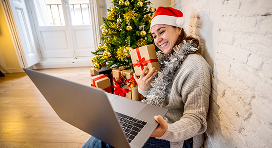 Woman on laptop holding a gift to the webcam